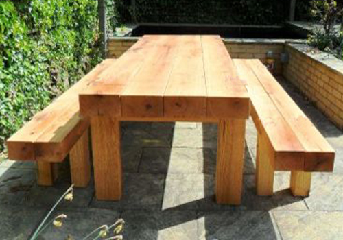 The block design of a solid red gum timber garden table and seats